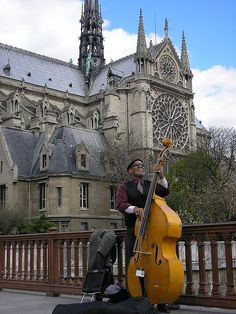 Ile de la cité, bass player on the 'Pont au double' and 'Notre Dame' cathedral, Paris IV. This bridge owes its name to the toll fixed at 'a double  denier', former French currency, for pedestrians crossing it.