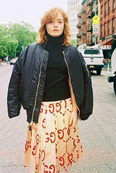 Mallory Merk in a black bomber jacket, sleeveless turtleneck, and GucciGhost silk skirt