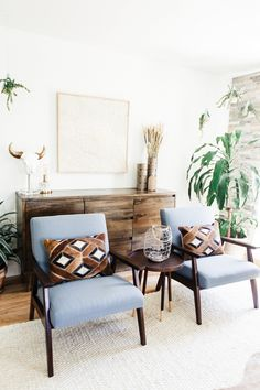 blue mid-century style chairs with calfskin geometric pillows adds to a family room filled with neutrals and natural textures with pops of color from plants