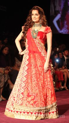 Actress Dia Mirza looked ethereal in a rich red and gold lehenga-choli as she posed for the cameras on the ramp. (Photo: Dilip Kagda)