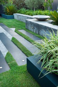 Interest is added to the horizontal plane with contrasting dark and light pavers separated by strips of lawn.  Cultivart Landscape Design