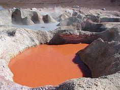A pool of reddish water/mud at the Geyser Sol de Mañana, Bolivia.