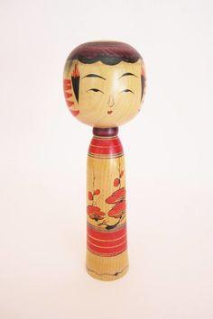 Traditional kokeshi doll, Yajiro style, with a beautifukl pattern of plum flowers branches.