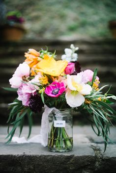| SPRING TROPICAL WEDDING | Amy's tropical spring bridal bouquet, made with bright flowers poppies, garden roses, anemones, fritillaria, scabious, delphiniums, lilac & eucalyptus for their beautiful wedding at Polhawn Fort on the coast of Cornwall.