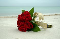 Red rose bouquet with navy blue wrap and gold accent ribbon.  Photo by Sunset Beach Weddings.