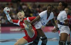 Heidi Loke of Norway, left, and Mariama Signate of France challenge during their women's handball preliminary match at the 2012 Summer Olympics, Saturday, July 28, 2012, in London.