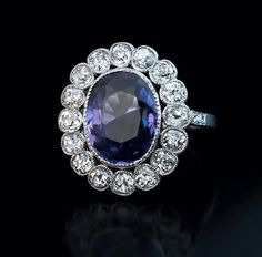 A Vintage Plum Sapphire and Diamond Platinum Engagement Ring, c. 1925. The milgrain platinum ring features a 5.41 ct natural sapphire with an unusual bluish-purple color. The sapphire is framed by 16 sparkling old European cut diamonds, the shoulders set with six old rose cut diamonds.