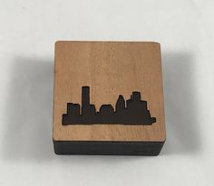 Houston skyline box made from unfinished birch wood, mahogany and acrylic. Layers of birch wood create the sides of the box and the lift off top is mahogany inlaid with translucent black acrylic. Each box is handmade by me and is unique. Perfect for hair pins, paper clips, keys, loose change, candy, small doodads you keep on your desk, etc. Keep on your night stand or coffee table for small keepsakes. Makes a lovely housewarming gift!  Dimensions are: 3 1/2 by 3 1/2 by 1 1/4 ta...