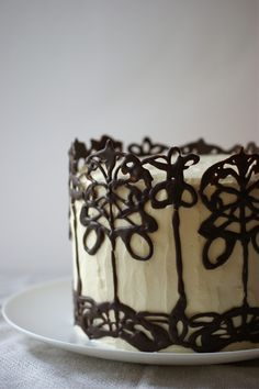 wow--this is the melt chocolate, pipe a design on parchment paper, freeze and peel off technique--but done so beautifully!  Website has instructions for making it bend around the cake (unnecessary if you do it in small sections, I think? I hope?) and also the good idea to draw a design under the parchment paper to pipe over.