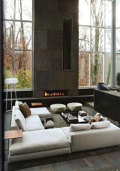 Modern, minimalist design in this tall space featuring stone fireplace surround, floor to ceiling windows, and white, U-shaped modern sectio...