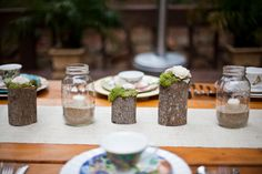 Loving this moss on tree trunk pillars for table centerpieces = affordable, rustic and eco-friendly.