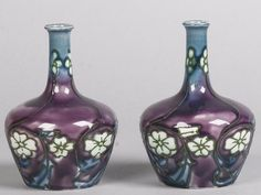 Minton Secessionist vases each of squat baluster form, with tube lined flowers on a purple and shaded blue ground, printed mark and number 33, 13cm high.