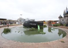 An armoured police riot van which was built to serve on the streets of Northern Ireland is on show in a small, stagnant pond