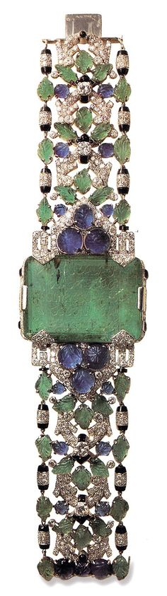 An Art Deco bracelet, by Cartier Paris, created in 1930 for the Aga Khan. Platinum; central enamel weighing 76 karats; band set with engraved sapphire and emerald leaves and onyx. The large emerald is engraved with text from the Quran. Image source: Cartier, by Hans Nadelhoffer #Cartier #ArtDeco #bracelet