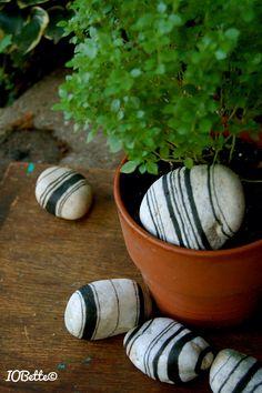 Hand-drawn designs to mimic fabric ticking on white tumble rocks using black India ink