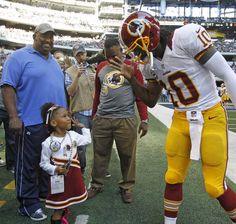 Washington Redskins quarterback Robert Griffin III (10) high fives his niece Jania, age four, before the game as the Washington Redskins play the Dallas Cowboys at Cowboys Stadium in Arlington, Texas on Thanksgiving Day, Thursday, November 22, 2012.–STAR-TELEGRAM/RODGER MALLISON
