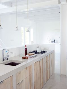 Big fan of this combination of a concrete countertop and wooden cabinet doors.