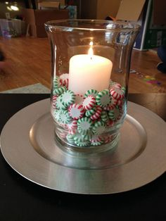 Easy Holiday Decor! Peppermints Spearmints unwrapped in a hurricane votive, with a pillar candle nestled in the center!