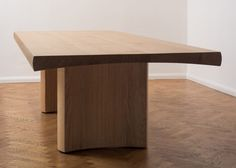 A minimalist, slab-legged oak dining table inspired by Japanese joinery. Hakone by Barber and Osgerby.
