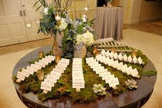 Nature inspired \\ Small logs cut with slits to hold table cards on a bed of moss. Carved initials on the centerpiece, nice touch.