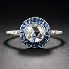 Like a sparkling geodesic dome, a half-carat rose-cut diamond, with the outer dimension of a modern round diamond, glistens from within a royal blue frame of faceted calibre-cut sapphires in this unusual and enchanting vintage style jewel, crafted in platinum and enlivened with tiny round diamonds on each shoulder
