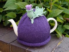 Hand knitted purple tea cosy with crocheted thistle flower and leaf attached. Made with Sirdar Wool Rich Aran which will keep the teapot nice and