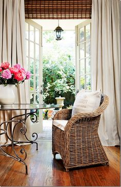 This charming French country vignette is highlighted by the round glass table with curvy legs & the open French doors with full draperies. The wicker chair adds to the indoor-outdoor feel. Charming... I can see this working for sliding doors, with the curtain panel in the middle of the window.