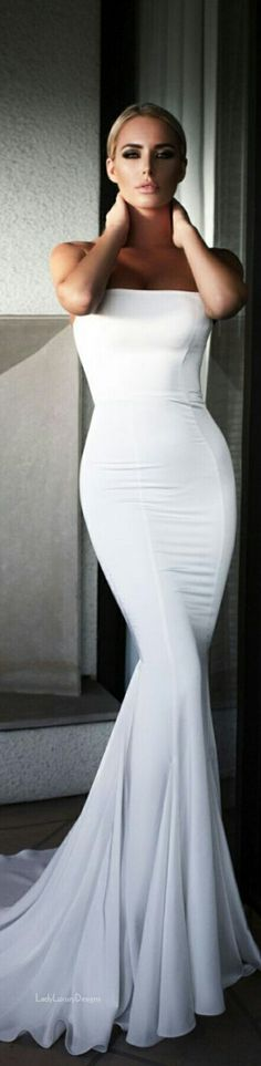 In a Sleek Cool Pose Dressed in a Classic White Evening Gown. LADY LUXURY.