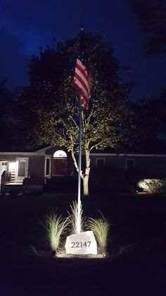 American flag pole with landscape lighting, flag stone address, and tall grass.