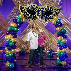 The Mysterious Mask Balloon Arch features a purple and gold mask accented with purple, green and gold balloons. Each cardboard Mysterious Mask Balloon Arch measures 9 feet wide x 9 feet tall and includes the mask and balloons shown.