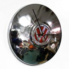 This hubcap clock is made from a recycled Volkswagen VW hubcap. The center of hubcap is red. As with most recycled hubcaps, this one has scuffs, pitting and dings adding to its charm. It has been cleaned and polished to shine. Clock diameter is 10. Clock runs on one AA battery -