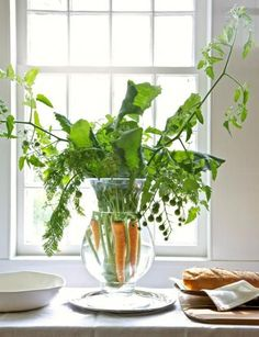 Edible centerpiece: Distilled water in a clean glass vase shows off scrubbed carrots and kohlrabi with leaves attached, along with large branches of green cherry tomatoes. More spring centerpieces: http://www.midwestliving.com/homes/seasonal-decorating/50-bright-and-easy-spring-decorating-ideas/?page=2