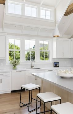 Such a stunning kitchen with transom windows + clerestory windows + large windows over the sink + black and white counter stools + wood stained island Kitchen Sink Window, Home, Home Kitchens, Kitchen Remodel, Kitchen Design, Grey Kitchen Island, Kitchen Island With Seating, Kitchen Interior, Stools For Kitchen Island