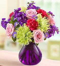 This majestic purple vase is filled with purple stock, pink roses, carnations and mums - a combination that celebrates Mom in grand style.