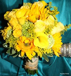 Here is an example of a bridal bouquet with yellow roses and sunflowers. This bouquet is perfect for a spring or summer wedding!