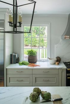 White and gray kitchen features light gray cabinets paired with calacatta marble countertops.