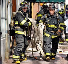 Firefighters drag a hose to the entrance of the Grill Room on Exchange Street Monday, after a fire started in the basement and spread to the walls of the building.