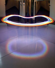 In this piece, titled Beauty Is In the Eye of the Collective, Morgana used a rounded mirror and neon lights to create the optical illusion of a floating circle. Standing at an angle, the viewer sees a full circle of lights and a rainbow projected onto the floor. But upon closer inspection and interaction with the piece, the open set-up reveals a new understanding of reality that is different from the viewer's initial impression.