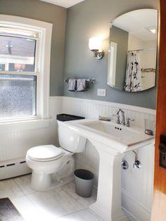 Elizabeth Bland designed this Classic Bathroom. The family decided on a deep soaker tub, a unique arched medicine cabinet, and a monochromatic color scheme. The floor tile is a porcelain made to look like stone. Classic white subway was chosen for the shower walls along with a linear marble border. To replace the bulky vanity, a pedestal sink was chosen. The overall design is cohesive, complements the home's style, and the homeowners love it!