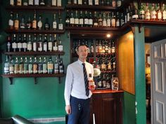 David the bar man in front of the famous whisky locker at The Craigellachie Hotel in Speyside