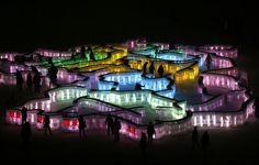 People visit a maze which was built by ice bricks and illuminated by coloured lights during a trial operation ahead of the 31st Harbin International Ice and Snow Festival in the northern city of Harbin, Heilongjiang province. The winter festival will be officially opened on January 5, 2015.