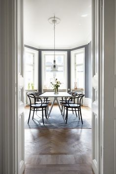 Curvy bentwood chairs (Le Corbusier / Thonet) are pretty in a high ceiling dining room with a large bay window.