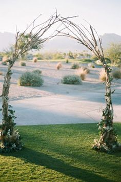 DIY outdoor ceremony arch with branches and flowers.