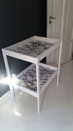 """Ikea Sniglar changing table hack. Painted white and covered with """"marble"""" plastic vinyl."""