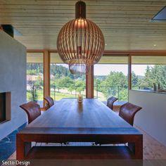 Das Esszimmer zeichnet sich durch eine helle und ruhige Atmosphäre aus, welche durch die bodentiefen Fenster und das gradlinige Design der Holzmöbel verstärkt.  - mehr auf roomido.com