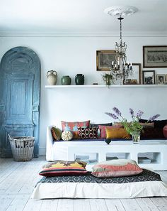 white wood floors, white sofa but a blue door and a lot of pillows. Must love the shelve too