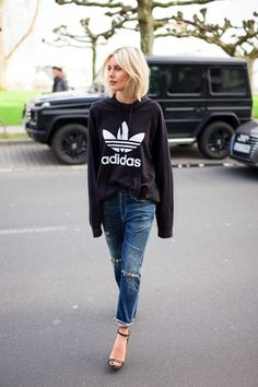 Athleisure is singlehandedly taking over the entire fashion industry and we couldn't be more thrilled about it. Blogger Lisa Rvd shows us a sporty chic way to pull off the trend in a black Adidas hoodie, ripped boyfriend jeans and heeled sandals with ankle straps.