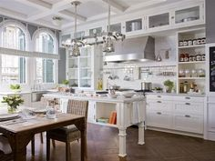 Beautiful kitchen. Love the windows, high beamed ceilings and the vertical cabinets