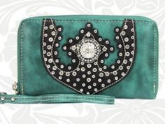 Blue-green genuine leather wristlet wallet with black leather and rhinestone design with a center concho. Zippers closed. Wrist strap included.