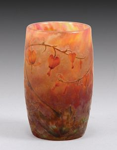 France, c. 1900  Decorated with orange ,red and green fuchscia flowers on mottled orange, red and yellow glass. Marked 'Daum Nancy' with cross of Lorraine in cameo.  9 cm high (Very minor chip)